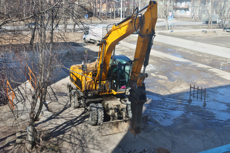 heavy industry: Yellow scrap tractor hammers asphalt on street at sunny spring day