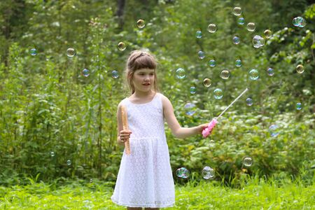 Pretty girl in white dress plays with soap bubbles in summer green forest Stock Photo