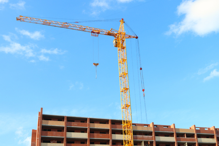 Working crane and red brick residential building with balconies under construction at sunny day Stock Photo