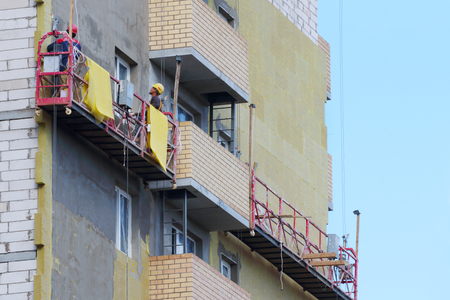 Workers in suspended cradle for facing facade of tall building under construction