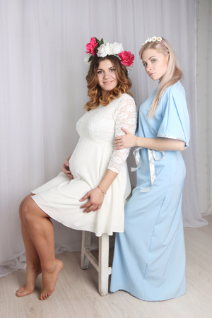 two beautiful girls in dresses with flowers in her hair in studio, one is sitting, other is standing
