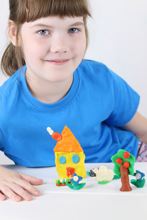 Girl sits with house, tree, flowers from plasticine on table in white room Stok Fotoğraf - 89718515