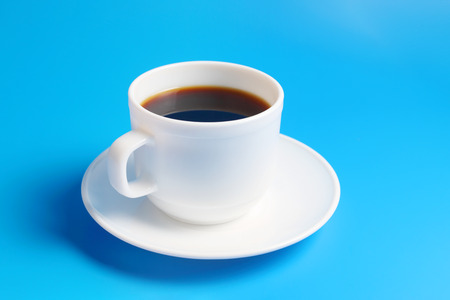 White cup with black coffee on a saucer on a blue background