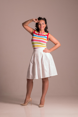 Beautiful woman in skirt with hairdo poses in grey studio, pin up style, full body Stock Photo