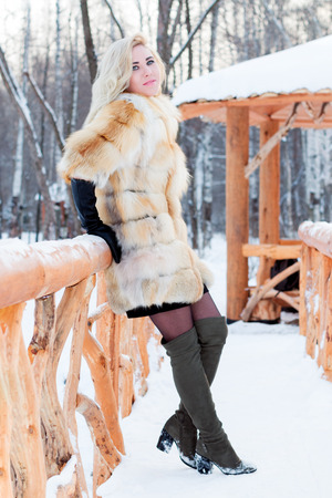 Pretty blonde in fur coat, leather gloves poses on wooden bridge at winter day in park with arbor