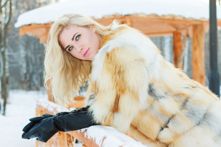 Pretty blonde in fur coat, leather gloves poses at winter day in park with arbor