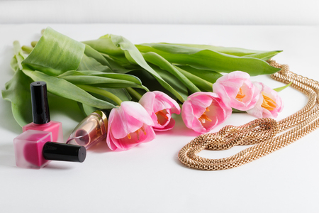 Pink tulips, bijouterie, cosmetics are on white table - spring female things