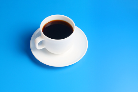 Simple white cup with black coffee on a saucer on a blue background