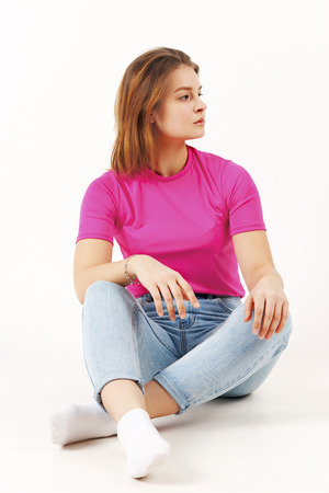 Girl teenager in pink t-shirt and jeans sits on floor in white studio, full body