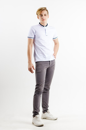 Handsome blond boy teenager in white shirt stands in white studio, full body