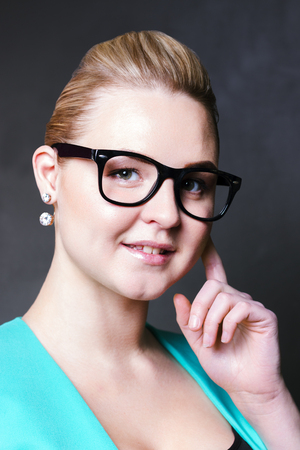 Pretty business woman in glasses and jacket smiles in black studio