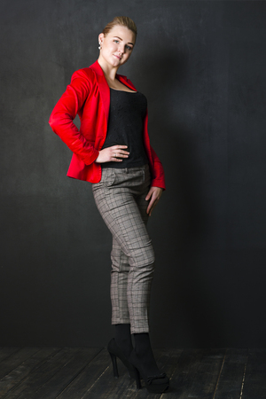 Pretty woman stands in red jacket in black studio, full body
