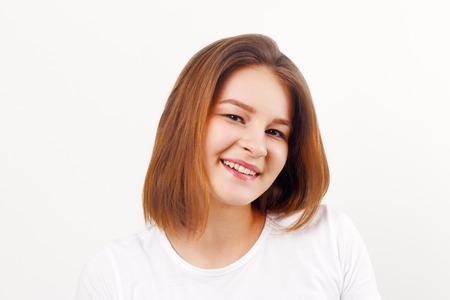Beautiful happy girl teenager in white t-shirt smiles in white studio Standard-Bild