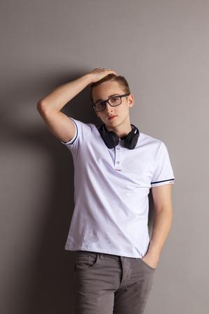 Handsome boy teenager with headphones stands near wall in grey studio