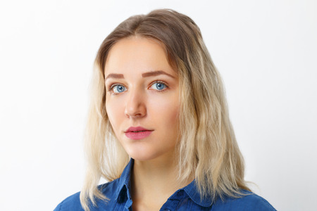 Pretty young girl  with make-up in blue shirt poses in studio Standard-Bild