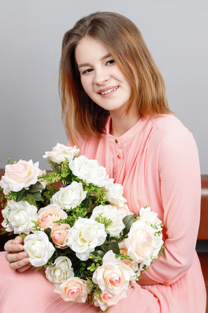 Happy girl teenager in dress sits on couch with flowers in grey studio