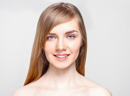 Pretty young woman with make-up smiles in studio, close up portrait Standard-Bild