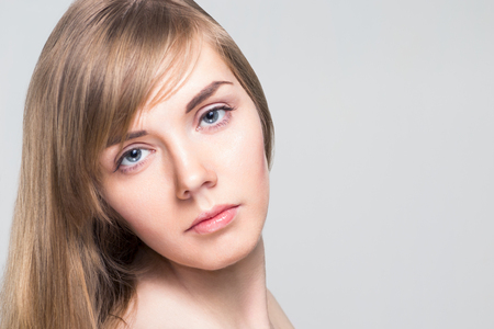 Pretty caucasian woman with long hair and pink lips poses in studio, close up portrait