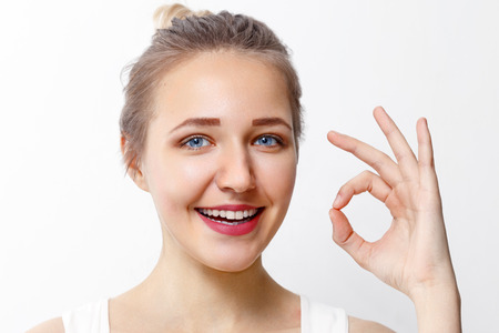 Pretty young girl with make-up shows Ok gesture in studio, close up portrait