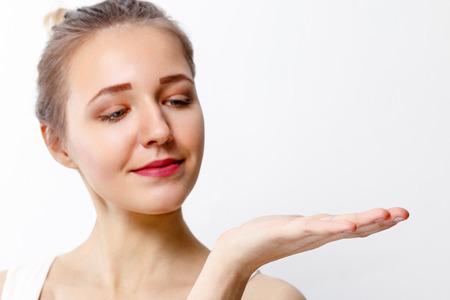 Pretty young girl with make-up shows palm in studio, close up portrait, focus on palm
