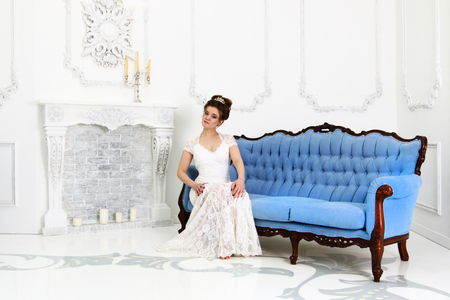 Pretty young bride in white dress sits on baroque sofa in studio with fireplace