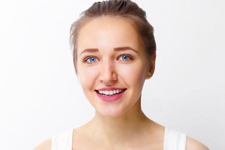 Pretty young girl with make-up smiles in studio, close up portrait