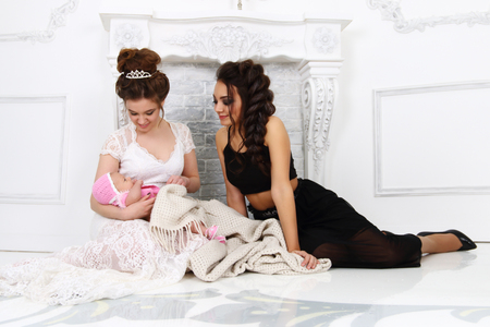 Pretty girls in white and black sits with baby near fireplace in white studio