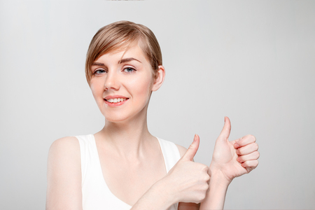 Beautiful young woman with make-up thumbs up and smiles in studio