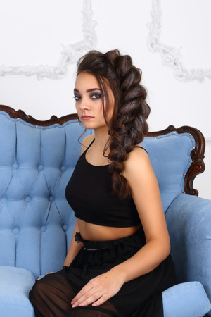 Pretty young girl in black sits on blue baroque sofa in studio with molding on walls