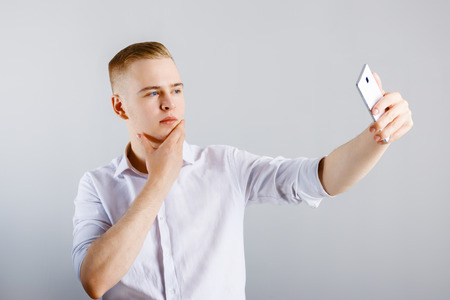 Young happy man in white shirt makes selfie with smartphone in studio