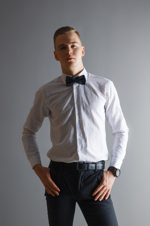 Handsome man in white shirt and bow tie poses in grey studio