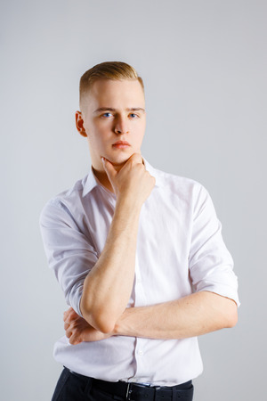 Young handsome caucasian man in white shirt touches his chin in studio