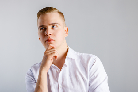 Young handsome man in white shirt touches his chin and thinks in studio Standard-Bild