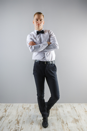 Handsome young man in white shirt and bow tie poses in grey studio, full body Foto de archivo