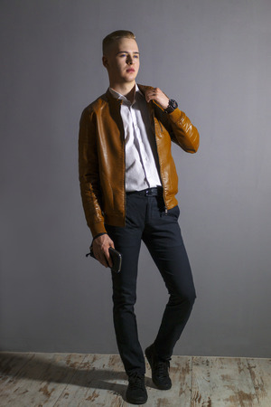 Young man in leather jacket poses with a purse in grey studio, full body