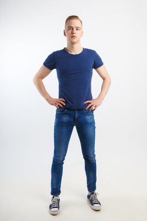 Young handsome man in blue shirt and jeans poses in white studio, full body