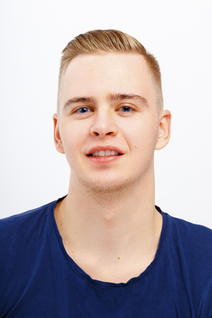 Young blond happy man in blue shirt smiles in studio, close up portrait
