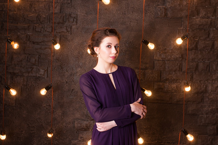 Pretty young brunette stands in studio with brick wall and lamps