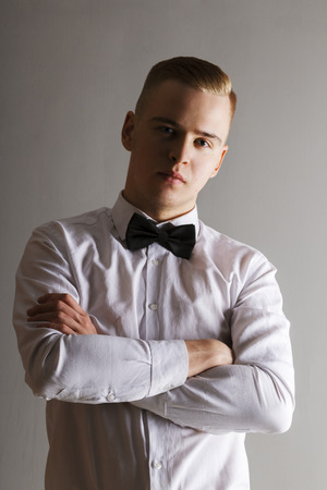 Handsome man in white shirt and bow tie poses with crossed arms in grey studio