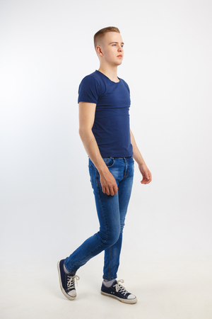 Handsome man in blue shirt and jeans goes in white studio, full body Foto de archivo