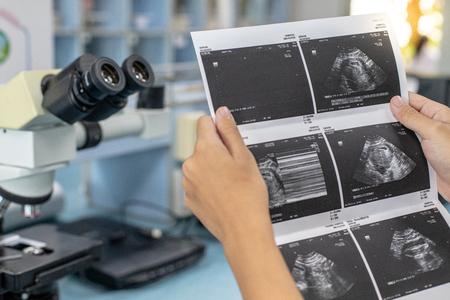 Médico que lee los resultados del ultrasonido de una mujer embarazada.