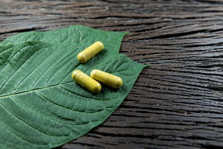 Mitragyna speciosa or kratom leaves with medicinal products on wooden table. 版權商用圖片