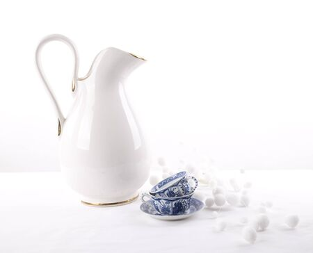 delftware: White pitche with two Delftware cups and white balls Stock Photo