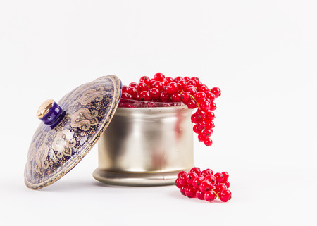 over the edge: Closeup the pearl bowl with lid full delicious red berries over the edge