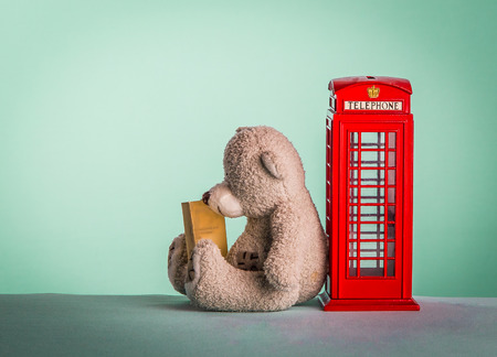 telephone box: Teddy bear sitting in the red telephone box and reads the information Stock Photo