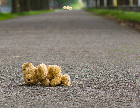 tardy: Teddy bear lies on the road Stock Photo