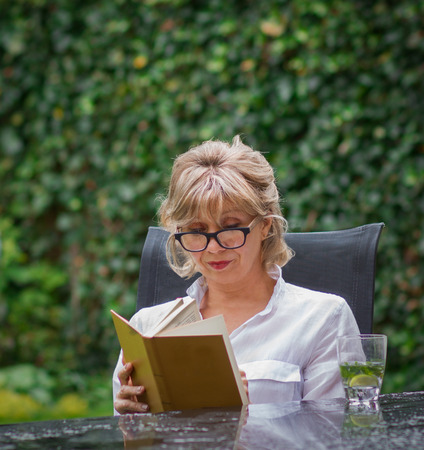 Attractive blonde woman aged in her garden, reading a serious book and drinking clean water with lemon