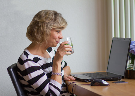 average age: Attractive middle-aged woman looking at the monitor and drinking water with lemon and mint