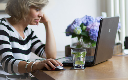average age: Attractive middle-aged woman working, using portable computer, looking at the monitor Stock Photo