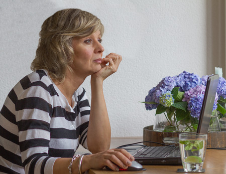average age: Attractive woman at work looking thoughtfully at the window